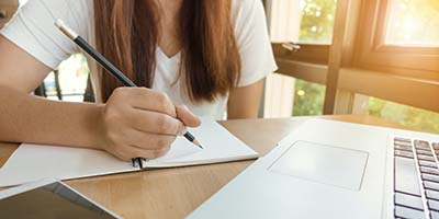 Woman writing course notes on paper